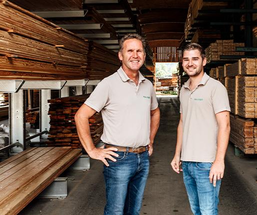Johann und Andreas Gar vor einem riesigen Lager an Bauholz am Standort in der Aumühle von Holz Gar.